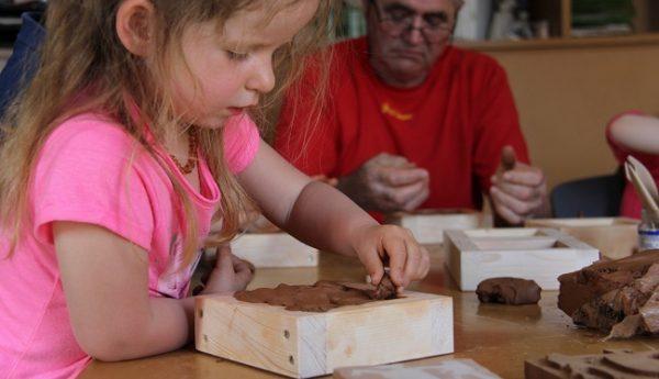 Une petite fille en train de réaliser son carreau en argile